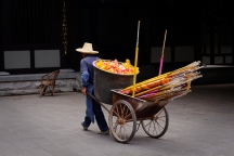 a man transporting incense in a temple in Guilin, China